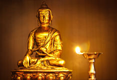 Golden Buddha with oil lamp Royalty Free Stock Image