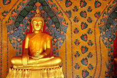 Golden Buddha and painting wall. Golden Buddha on painting wall in arcade at temple, Bangkok, Thailand royalty free stock photography