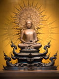 Golden Buddha sculpture in lotus position sitting Stock Photos
