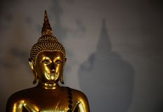 Golden buddha with shadow. Background Royalty Free Stock Image