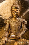 Golden Buddha sitting in front of a gong Royalty Free Stock Photography