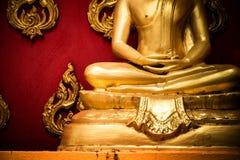 Golden Buddha sitting in meditation Royalty Free Stock Image