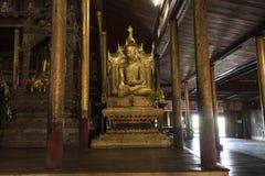 Golden buddha sitting. Myanmar. Ancient wooden temple with a golden buddha sitting. Inle Lake, Myanmar royalty free stock image