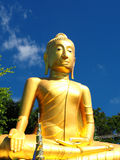 Golden Buddha soaring into blue sky Stock Photo