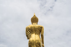 Golden Buddha standing on a mountain with white cloud background Stock Photos