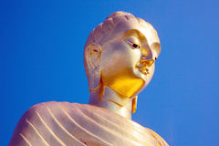 Golden Buddha statue against blue sky Stock Photography