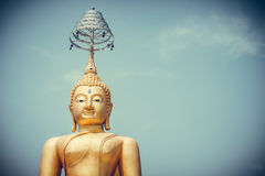 Golden Buddha statue against blue sky in vintage tone with vigne Royalty Free Stock Photos
