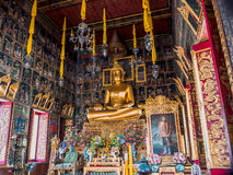 Golden Buddha statue with ancient mural painting around. Golden Buddha statue in large temple and with ancient mural painting around Stock Photos