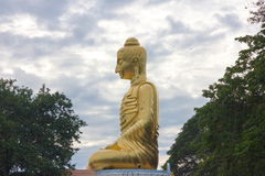 The golden buddha statue on blue sky. At Prachuab kirikhan, Thailand Royalty Free Stock Photography