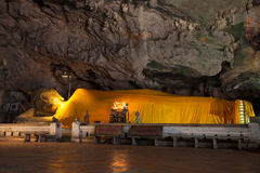 A golden Buddha statue in the cave.  Stock Photo