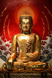 Golden buddha statue. Chinese style golden buddha with cross-legged sitting position on red background Royalty Free Stock Images