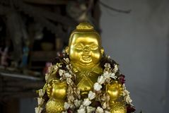 Golden buddha statue with flower rings Royalty Free Stock Photo