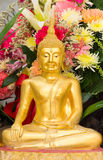 Golden buddha statue. Flowers background Royalty Free Stock Photography