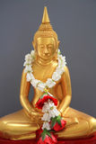 Golden Buddha statue with garland ob gray Royalty Free Stock Image