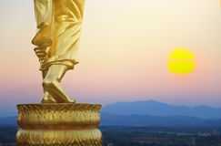 Golden buddha statue in Khao Noi temple Nan Province Thailand. Sunrise nature and golden buddha statue in Khao Noi temple Nan Province Thailand royalty free stock image
