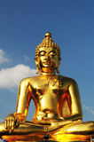 Golden Buddha statue. Large golden Buddha statue with blue sky and cloudscape background Royalty Free Stock Image