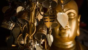 Golden Buddha statue with metal leaves of desires. Buddhist consciousness. Royalty Free Stock Photo