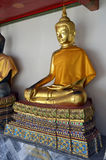 Golden Buddha statue with an orange cloth in Wat Pho. Bangkok, Thailand royalty free stock photography