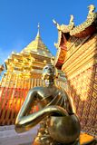 Golden buddha statue and pagoda against clear blue sky
