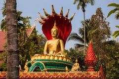 Golden Buddha statue seated on lotus flower. VIENTIANE, LAOS - MARCH 16, 2013: Golden Buddha statue seated on lotus flower at Buddhist temple Wat That Luang Tai Stock Photo