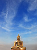Golden Buddha statue shining in the sun Stock Image