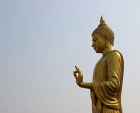 Golden buddha statue. On sky background royalty free stock photos