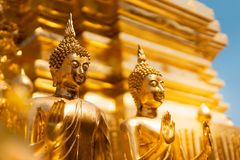 Golden buddha statue whith blurred golden pagoda background, selective focus. Buddhist holy day concept stock image