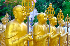 Golden Buddha statues. Along the stairs leading to the Ten Thousand Buddhas Monastery and landscape with green trees in the background in Thailand Royalty Free Stock Images