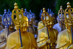 Golden Buddha statues. Along the stairs leading to the Ten Thousand Buddhas Monastery and landscape with green trees in the background in Thailand Stock Photo
