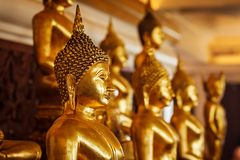 Golden Buddha statues in buddhist temple royalty free stock photography