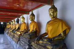 Golden Buddha statues with orange clothes in Wat Pho. Bangkok, Thailand stock photography