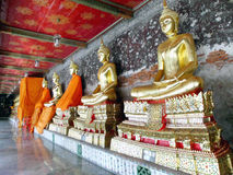Golden Buddha statues in a row inside the temple hall of Wat Suthat Stock Photos