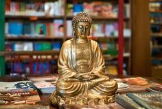 A golden Buddha statuette among yoga magazines Royalty Free Stock Photography