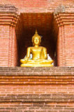 Golden Buddha on stone wall Royalty Free Stock Photography