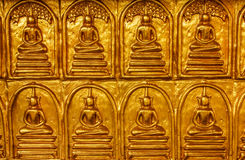 Golden buddha wall. In church of the temple Royalty Free Stock Image
