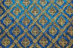 Golden buddha wall decoration. Wallpaper of temple in Thailand made from golden buddha sculpture and bue tile Stock Photo