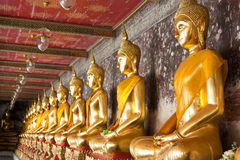 Golden buddhas lined up. Along the wall in temple Royalty Free Stock Images