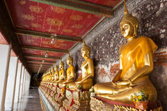 Golden buddhas lined up. Along the wall in temple Royalty Free Stock Photo