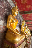 Golden buddhas lined up. Along the wall in temple Stock Photo
