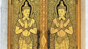 Golden buddhas praying. Door of a palace in thailand Stock Photo