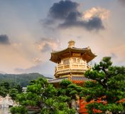 Golden buddhism tower with sky and light. Golden Chinese buddhism tower with beautiful cloud and light in China Royalty Free Stock Images