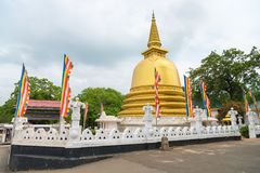 Golden buddhist dagoda or stupa monument. With white fence and flags around on the front of Dambulla cave temple on Sri Lanka island Stock Image