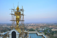 Golden buddhist sculpture under renovation progress on top of hill Royalty Free Stock Photo