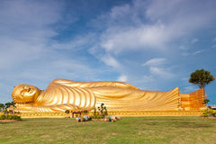 Golden Buddhist statue. Golden lying Buddhist statue in green field with blue sky and cloudscape background Stock Photography