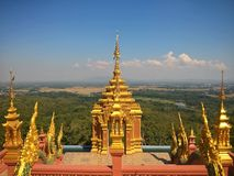Golden Buddhist temple on a hilltop. Golden Buddhist temple in Lampang, Thailand.  The temple was located on a hilltop Stock Image