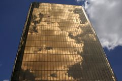 Golden Building Reflections. White clouds reflect on a golden office building.Perspective makes building appear to rise like a pyramid towards the sky Stock Images