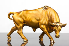 Golden Bull. Sclupture on grey glass Stock Photography