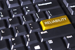 Golden button with text of reliability Stock Photography