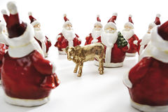 Golden calf, surrounded by Santa Clauses Stock Photo
