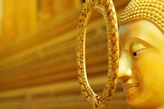 Golden calm face of Buddha statue with golden background. Have some space for text or wording about Principles stock image